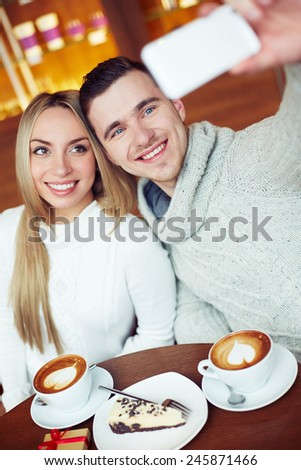 Cheerful guy and girl taking their selfie while resting in cafe - stock photo