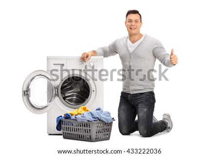 Cheerful guy doing laundry and giving a thumb up isolated on white background