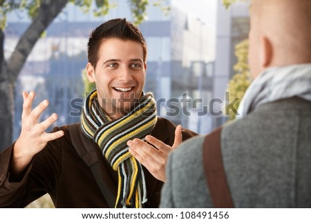 Cheerful guy gesturing to friend in conversation, standing outdoors, wearing scarf, smiling. - stock photo