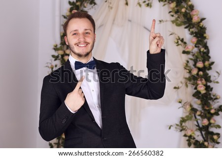 cheerful guy in a classic suit and bow tie shows your text - stock photo