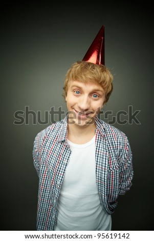 Cheerful guy in a cone cap being ready for fool�s day celebration - stock photo