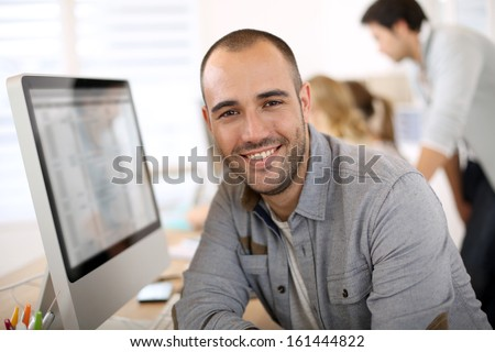 Cheerful guy sitting in front of desktop computer - stock photo