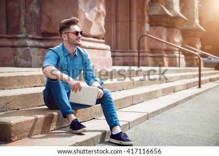 Cheerful guy sitting on the footsteps - stock photo