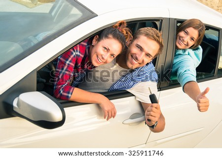 Cheerful guy with two girls in the car ready for a trip - Group of friends are excited for the next holiday destination - Concept of freedom, inclusion, transport and travel, main focus on guy face - stock photo