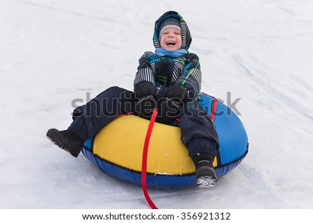 Cheerful handsome boy riding a roller coaster. Toddler walking in the snow in winter. The child laughs and smiles in winter park. - stock photo