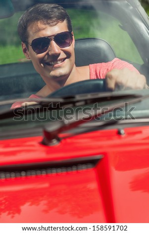 Cheerful handsome man driving his cabriolet on a sunny day - stock photo