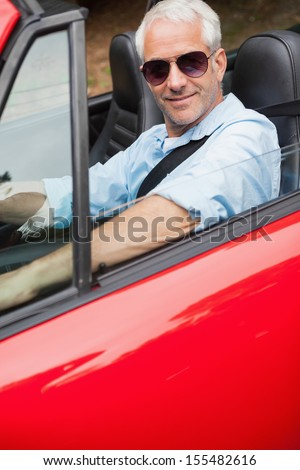 Cheerful handsome man driving his red convertible on a bright day - stock photo