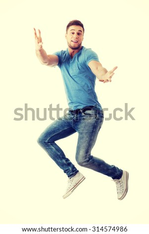 Cheerful handsome man jumping for joy. - stock photo