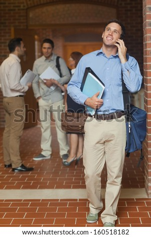 Cheerful handsome mature student phoning with his smartphone walking through the corridor - stock photo
