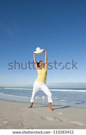 Cheerful happy and attractive looking senior woman enjoying retirement at beach, isolated with ocean and sky as background and copy space.