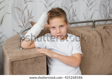 Cheerful happy child with a broken arm in the home environment . The cast on his hand a beautiful little boy. Injury to a child is bored at home. - stock photo