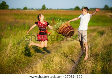 Cheerful happy couple having fun outdoors in summer meadow. Family playing in field. Togetherness. Picnic. Man and woman jumping. Laughing, smiling people - stock photo