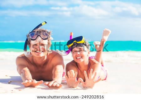 Cheerful happy couple having fun snorkeling, lying on summer beach sand with snorkel equipment