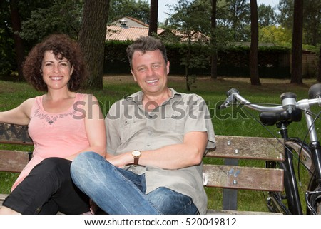 Cheerful happy couple together on a bench with bikes