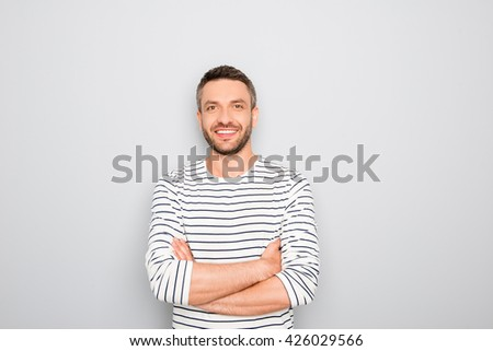 Cheerful happy guy with crossed hands on white background - stock photo