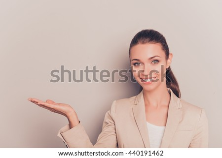 Cheerful happy woman making advertisement and gesturing with hand - stock photo
