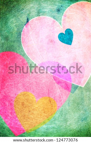 Cheerful hearts in pastel colors on a green background. Vintage, scratchy look. - stock photo