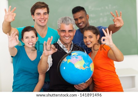 cheerful high school geography students and teacher giving ok hand sign in classroom - stock photo