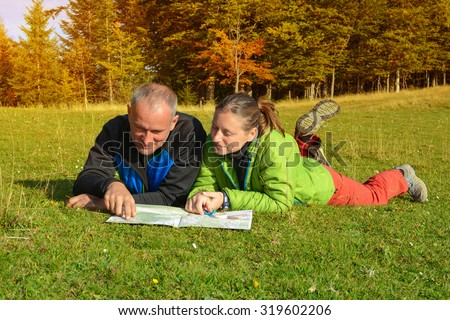 Cheerful hikers are  planning their route. Smiling man and woman are lying in the autumn forest. Hikers couple with map. - stock photo