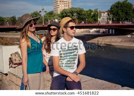 Cheerful Hipster Friends At The River Shore In City On Sunshine
