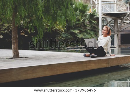 Cheerful hipster girl enjoying rest and good day after work on portable laptop computer during spring weekend, smiling woman sitting with open laptop computer during free time in modern hotel outdoors - stock photo