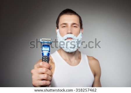 Cheerful hipster guy is holding a razor and showing it to the camera with seriousness. He decided to shave his beard. The guy has shaving foam over his face. Isolated on grey background - stock photo