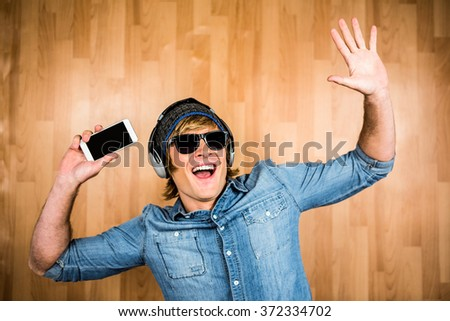 Cheerful hipster listening to music with hands up - stock photo