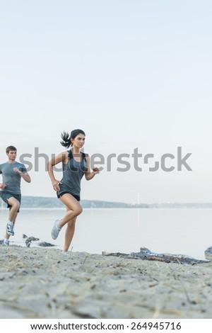 Cheerful Hispanic Caucasian couple running on beach at morning - stock photo