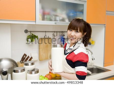 cheerful housewife holding a kitchen storage tin - stock photo