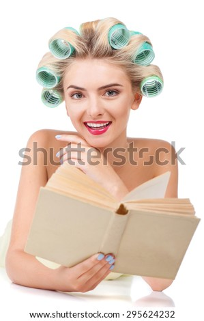 Cheerful housewife is holding book and lying. She is smiling and looking towards. The lady has rollers in her hair. Isolated on background - stock photo