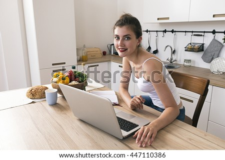 Cheerful housewife smiling at camera at kitchen table with laptop,food and drink