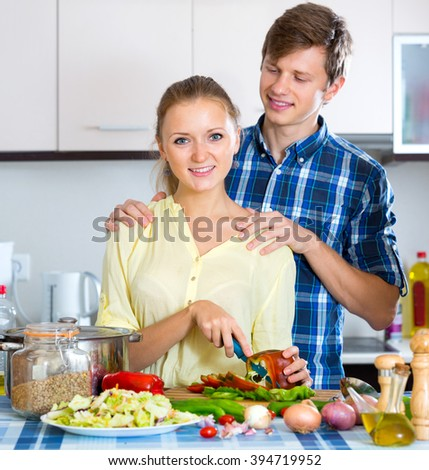 Cheerful husband helping wife to prepare healthy dinner - stock photo