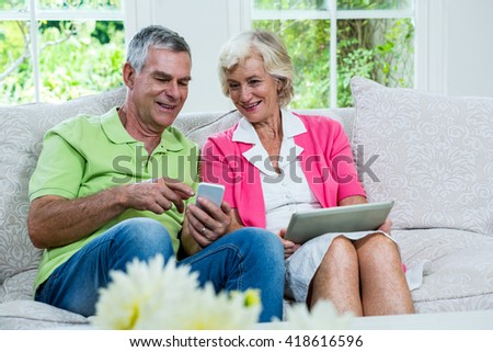 Cheerful husband showing mobile phone to senior woman on sofa - stock photo