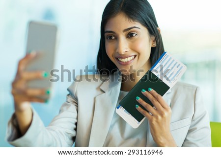 cheerful indian businesswoman at airport taking self portrait with smart phone - stock photo