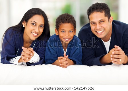 cheerful indian family lying on bed together - stock photo