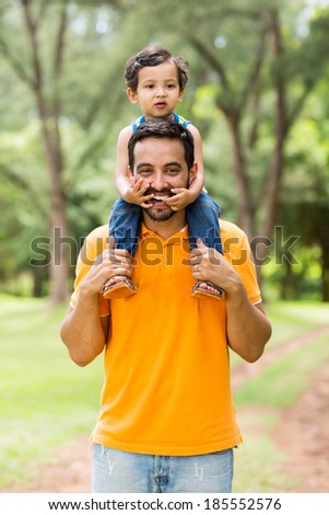 cheerful indian father carrying son on his shoulders in the park - stock photo