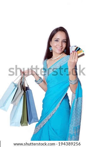 Cheerful Indian female with credit cards and shopping bags in hand.