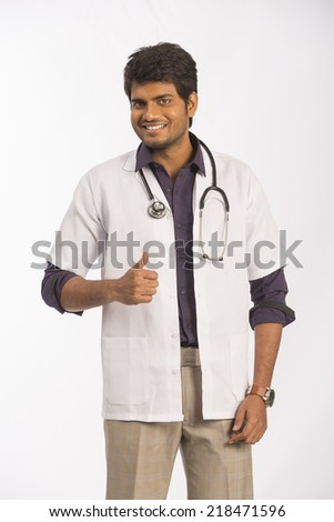 Cheerful Indian male doctor showing success sign on white background - stock photo