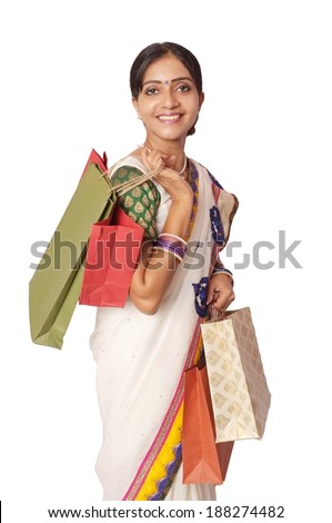 Cheerful Indian Woman happy after shopping. Portrait of a happy Asian female in Saree carrying a lot of shopping bags on isolated white background. - stock photo
