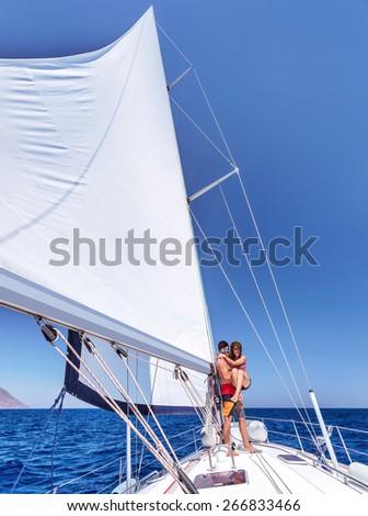 Cheerful joyful couple having fun on sailboat, enjoying wonderful summer adventure, honeymoon in sea cruise, love and happiness concept - stock photo