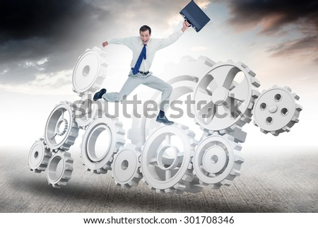 Cheerful jumping businessman with his suitcase against blue sky - stock photo