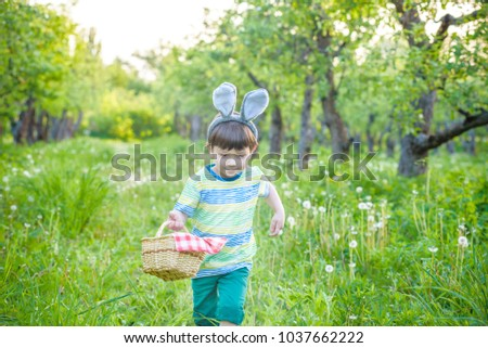 cheerful kid holding basket full of colorful easter eggs standing on the grass in the park after egg hunt. Cute smiling boy having fun during traditional spring religious holiday.