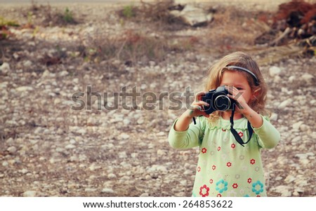 Cheerful kid holding old camera - stock photo