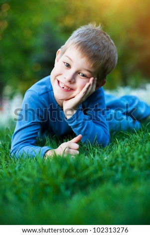 cheerful kid laying on the green grass - stock photo