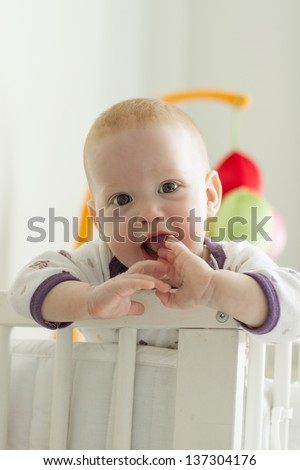 Cheerful kid looking out of his bed - stock photo