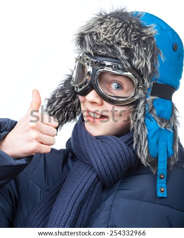 Cheerful kid wearing winter clothes showing thumb up on white background - stock photo
