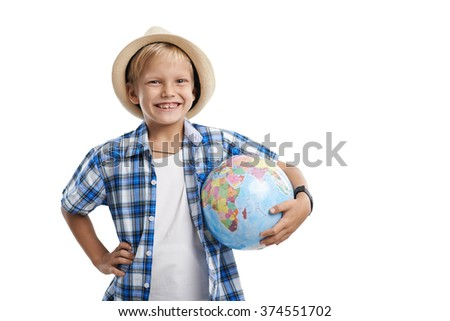 Cheerful kid with globe in his hand looking at camera: travelling and adventures concept - stock photo