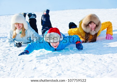 Cheerful kids and their mother sliding down the snowy hill - stock photo