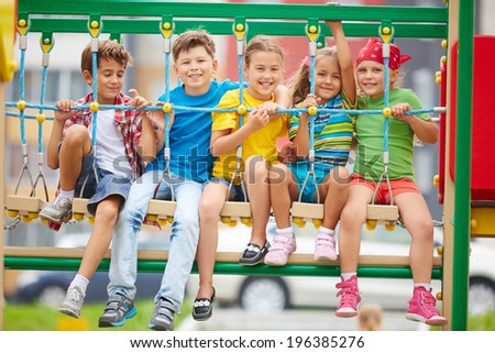 Cheerful kids sitting on swing and looking at camera - stock photo