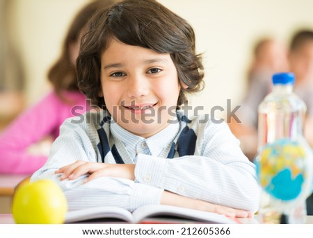 Cheerful kids sitting with apple and globe on desk in classroom - stock photo